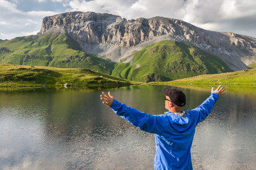 Travel man standing with raised hands near the beautiful mountain lake