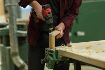 Male carpenter using drill machine at workshop
