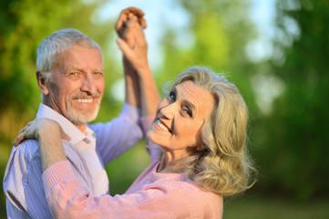 portrait of beautiful caucasian senior couple  in the park danci