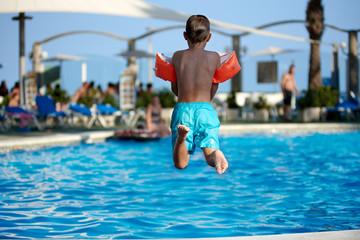 Caucasian boy having fun jumping into the pool.