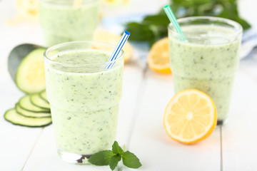 Refreshing green cucumber, yogurt, mint and lemon smoothie in glasses, photographed on white wood (Selective Focus, Focus on the front of the glass rim and the tip of the blue straw)