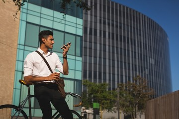 Businessman talking on mobile phone outside office premises