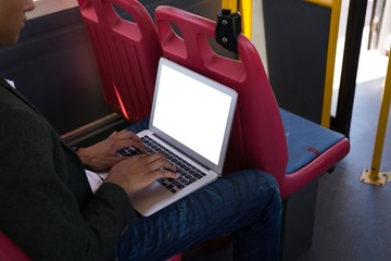 Businessman using laptop while travelling in bus