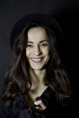 Happy tender girl. Photo of gorgeous young brunette woman  in black hipster hat