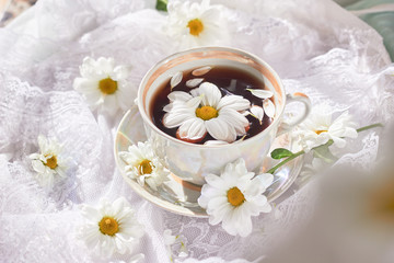a cup of tea with chamomile on a table with a white tablecloth and flowers