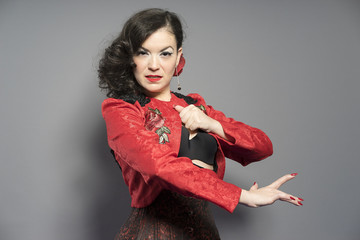 Passion, Spanish flamenco dancer. Typical Spanish brunette woman with red jacket and Spanish folk dance dress