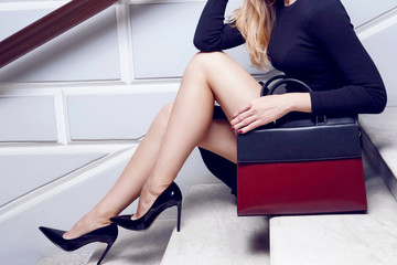 Model close up legs in high heel with fashion leather red bag Wall mural