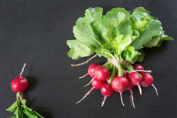 Red radish with foliage on black slate dish as background. Top view.