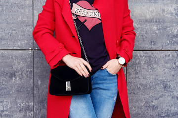 Wall Mural - Autumn outfit woman in red trendy coat and jeans with black small clutch