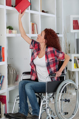 disabled woman struggling reaching a book on top shelf