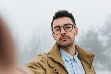 Serious young male is making self portrait on camera outdoors. Handsome traveler man wear coat, blue shirt and eyeglasses making selfie and smiling while standing against grey misty nature background.