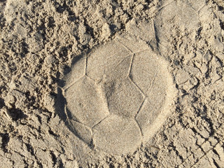 Print of a football in the sand