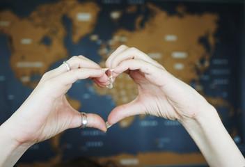 Manos formando un corazón sobre un mapa mundi