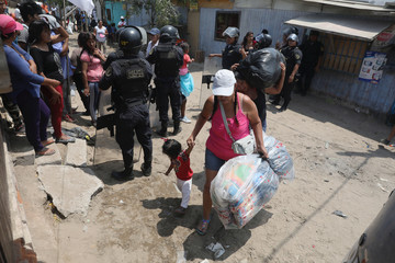 Police guard, as people carry their belongings after police evicted squatters from a land in Villa El Salvador, on the outskirts of Lima