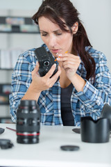 female photographer lens and camera cleaning