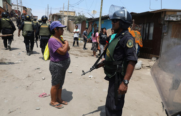 Police guard the area after evicting squatters from a land in Villa El Salvador, on the outskirts of Lima