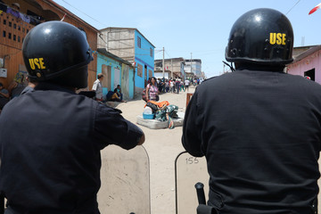 Police guard as people carry their belongings after police evicted squatters from a land in Villa El Salvador, on the outskirts of Lima