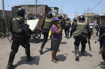 Police patrol a street after evicting squatters from a land in Villa El Salvador, on the outskirts of Lima