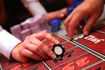 Casino player holding one chip