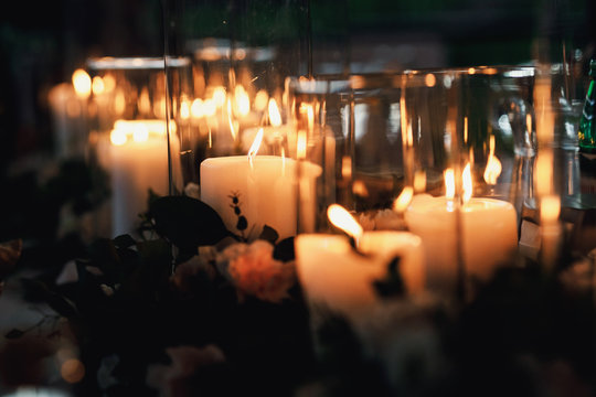 many candles in glass vases on the floor on hipster style weddin