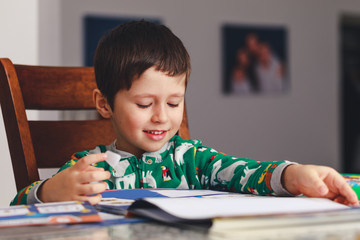 Young little boy reading a book while sitting at table, indoor shoot. Little boy having fun during studying. Best picture for child education concept.