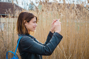 Beautiful urban brunette woman taking photo of countryside landscape