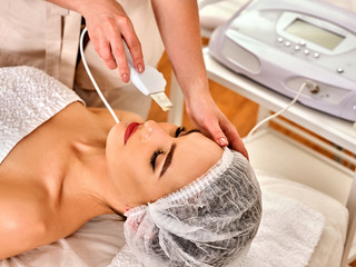 Skin care of ultrasound facial peeling. Ultrasonic cleansing procedure. Top view of beauty treatment of woman. Beauty cosmetology in spa salon.