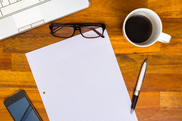 Working desk with Laptop, Blank Paper, Pen, Mobile Phone, Glasses, Coffee