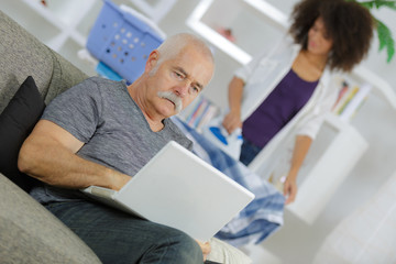 senior man with laptop and home help ironing