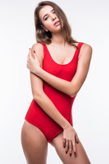 Sexy brunette woman posing in fashionable red swimwear with fit body isolated on white