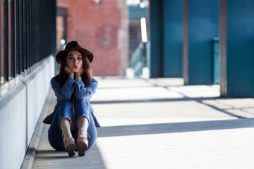 beautiful girl in a hat sending an air kiss. portrait of pretty woman sitting on the ground. Copy space for your text