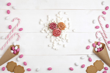 Frame Candies, cookies,Marshmallows and Lollipops Top view White wooden Background