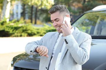 Man in formal wear talking on phone near car outdoors