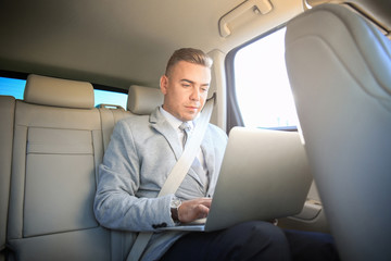 Man in formal wear with laptop in car
