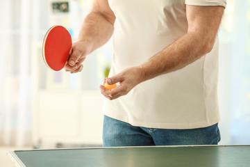 Senior man playing table tennis indoors