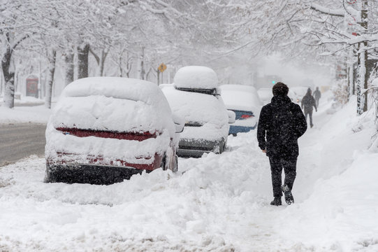 City street and cars covered in snow during winter storm in Montreal, Canada