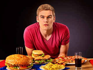 Man eating pizza and hamburger. Student consume fast food. Male trying to eat lot of junk. Advertise fast food on black background.