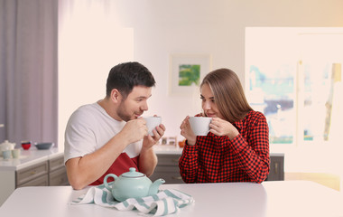 Cute young lovely couple drinking tea in kitchen