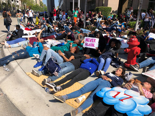 Students from Broward County high schools stage a die-in on a sidewalk in downtown Fort Lauderdale