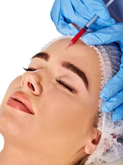 Filler injection for female forehead face. Plastic aesthetic facial surgery by doctor in beauty clinic. Beauty woman giving njections. Doctor in medical gloves with syringe injections.