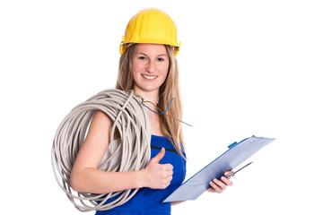 """Junge Elektrikerin in Arbeitskleidung, """"Daumen hoch"""""""
