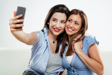 Two cute young woman taking a selfie and having fun