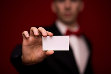 Stylish man in suit hold white business card on red background, focus on business card. Business concept