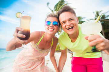 happy young couple with cocktails having fun by the beach