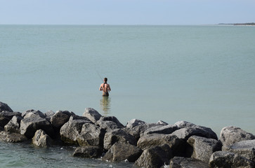 Young man fishing alone in the calm sea, sunny day.