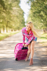 Beautiful cheerful young blonde women going on holiday. Happy female traveler dragging fully packed suitcase along the road