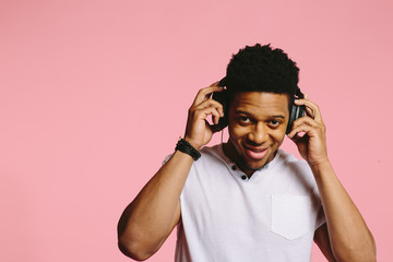 Portrait of a cool guy with headphones smiling and looking  at camera, enjoying music, on pink background