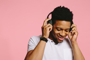 Portrait of a smiling guy in white shirt  listening to music and looking down, isolated on pink background