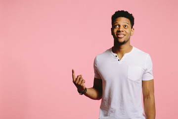 Portrait of an attractive cool guy pointing and looking up, isolated on pink