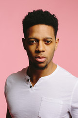 Close up of a cool African American guy in white shirt on pink background